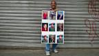 Ein Mann präsentiert in Venezuelas Hauptstadt Caracas ein Plakat mit Bildern von Hugo Chavez.