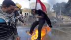 Ein protestierender Ägypter versucht vor Flammen zu fliehen, nachdem er vor dem Präsidentenpalast in Kairo eine Anti-Mursi-Flagge angezündet hatte.