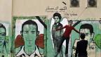 Jugendliche vor Wandbildern in einer Strasse von Kairo.