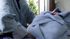 Eine Frau legt ein Kleinkind in das sogenannte Babyfenster.