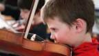 Ein Junge probiert, wie es ist auf einer Geige zu spielen.