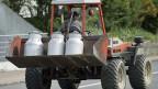 Ein Landwirt ist mit Traktor und Milchkannenunterwegs in die Käserei.