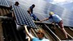 Jugendliche montieren Solarzellen auf einem Scheunendach Ruswil.
