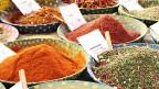 Auslage mit vielen verschiedenen Gewürzen in grossen farbigen Schalen.