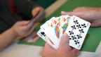 Eine Hand, die fünf Jasskarten hält.