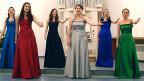Sechs Damen in langen Abendkleidern unterschiedlicher Farbe.