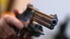 Nahaufnahme: Pistole wird in die Kamera gehalten