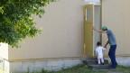 Asylbewerber mit Kind vor einer Unterkunft