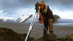 Mann mit optischem Gerät, dahinter Eisberg.