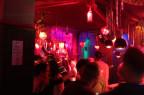 Szene in einem Club mit schummrigem Licht und Menschen.
