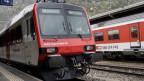 Ein Zug steht an einem Bahnhof.