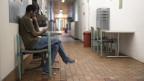 Gang in einer Asylunterkunft, ein Asylsuchender sitzt auf Stuhl und blickt auf Handy