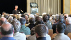 Blick von hinten auf Publikum, vorne ein Redner