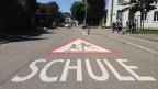 Strasse, Aufschrift Schule am Boden, Schüler im Hintergrund