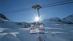 Bergbahn-Gondel vor schneebedeckten Gipfeln und Pisten.
