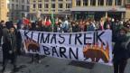 Menschenmenge auf grossem Platz. Zwei Schülerinnen halten ein Transparent: «Berner Klimastreik».