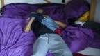 Ein Mann liegt auf einem Bett und spielt mit seinem Kind.