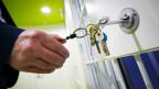 Eine Hand schliesst mit einem Schlüssel eine Tür auf.