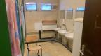 Blick in ein sehr einfaches und teilweise schmutziges Badezimmer mit mehreren Duschen und Lavabos