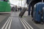 Passanten mit Koffern warten auf die Vorbeifahrt eines Trams.