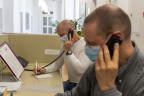 Zwei Männer mit Masken und Telefonhörern am Ohr