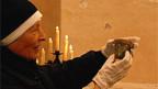 Die Priorin des Klosters nimmt das Reliquienglas aus dem Altar