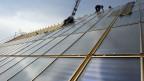 Auf einem steilen Dach werden Solarpanels montiert.