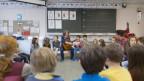 Kinder sitzen in einem Schulzimmer im Kreis.