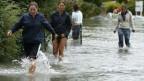 Menschen gehen auf einer überschwemmten Strasse.