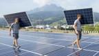 Zwei Arbeiter tragen Elemente einer Photovoltaik-Anlage auf der Luzerner Allmend.