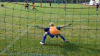 Ein Knabe steht als Torhüter auf einem Fussballplatz