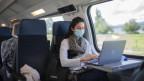 Eine Frau im Zug trägt eine Gesichtsschutzmaske.