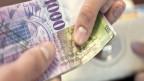 Zwei Hände halten mehrere 1000 Franken