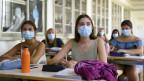 Schülerinnen mit Schutzmasken.