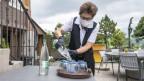 Kellnerin mit Maske schenkt Wasser ein