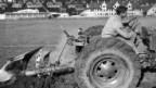 Ein Bauer pflügt im Jahre 1941 im Rahmen von Friedrich Traugott Wahlens Anbauplan für die Versorgung des Landes während des Zweiten Weltkriegs in Zürich einen Sportplatz.