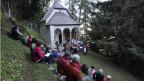 Die Bewohner von Fiesch und Fieschertal hören den religiösen Gesängen des Fieschertaler Chors zu, bei der Kapelle «Notre-Dame» in Fiesch.
