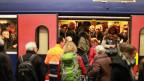 Pendler steigen in einen überfüllten Zug ein.