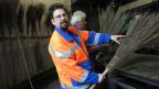 Martin Stucki (Bildvordergrund) bindet mit seinem Schichtleiter Besen.