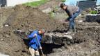 Exhumator an der Arbeit auf dem Grabfeld