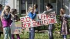 Kinder demonstrieren mit Transparenten vor dem Winterthurer Schulhaus Brühlberg.