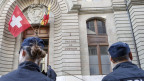 Zwei Polizisten stehen vor einem grauen Gebäude mit der Aufschrift «Palais de Justice»