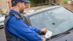 Ein Polizist steckt einen BUssenzettel unter einen Scheibenwischer.