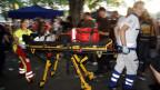 Eine verletzte Person wird von Rettungsleuten geborgen.