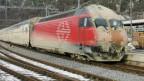 Ein dreckiger Zug verlässt den Lötschbergtunnel.