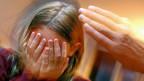Kind schützt seinen Kopf vor einer Ohrfeige