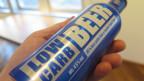 Bierflasche aus Aluminium mit blauer Aufschrift.