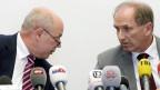 Zwei Männer an einer Pressekonferenz.