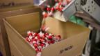 Rote Lindt-Schokoladekugeln werden in eine Kiste gefüllt.