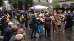 farbig angezogenen Menschen gehen durch die Zürcher Altstadt